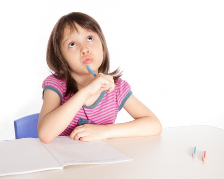Child at desk with pencils and notebook Foto de archivo