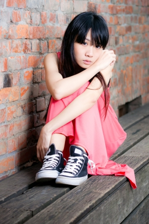 Young Asian woman sitting by red brick wall feeling depressed and sad