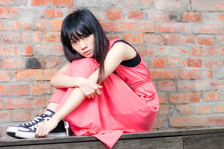 Young Asian woman sitting by red brick wall feeling depressed and sad photo