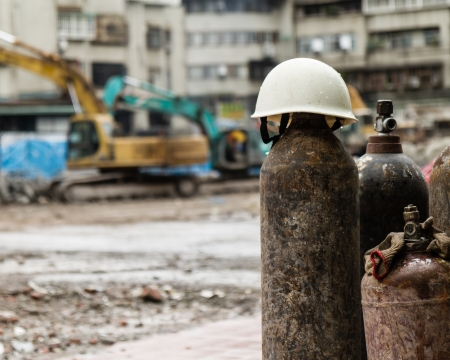 Hardhat on a gas cylinder at a construction site with rubble and trucks demolishing photo