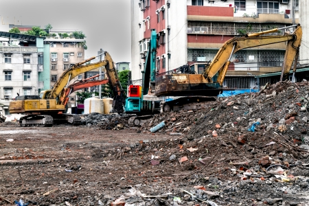 Construction site with rubble and trucks demolishing