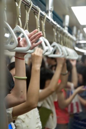 handle: Hands on hand grips in subway coach