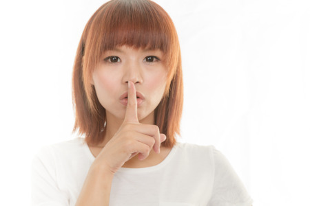 Attractive woman making a keep  quiet hand gesture , isolated on white Stock Photo - 23844564