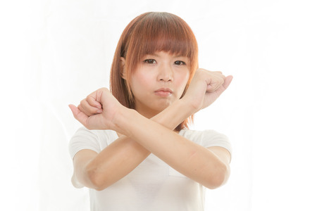 Young Asian woman making stop gesture over white background