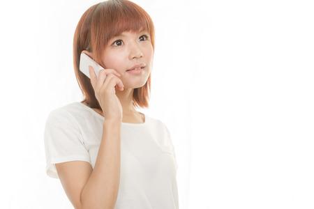 Asian female holding cordless phone