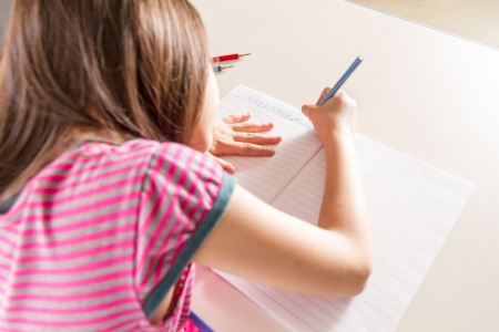 Young girl doing homework in a notebook Stock Photo