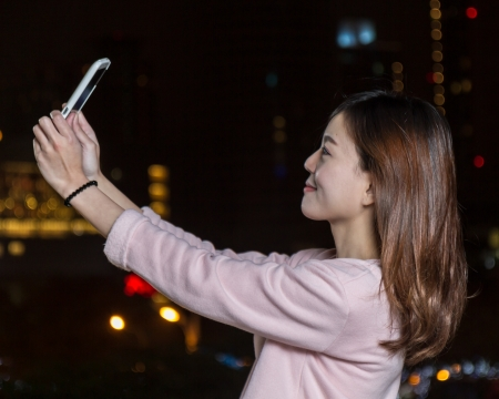Beautiful Malaysian female with bright lights of city in background Foto de archivo