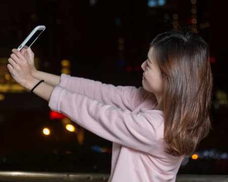 Beautiful Malaysian female with bright lights of city in background Stock Photo