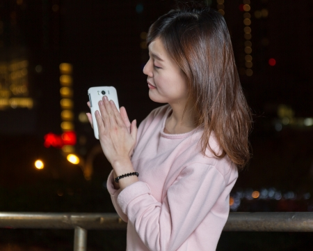 Beautiful Malaysian female with bright lights of city in background photo