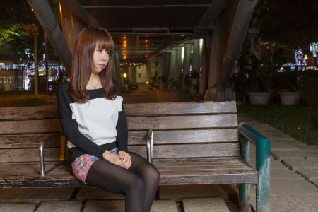 Japanese female looking sad sitting on a brown park bench
