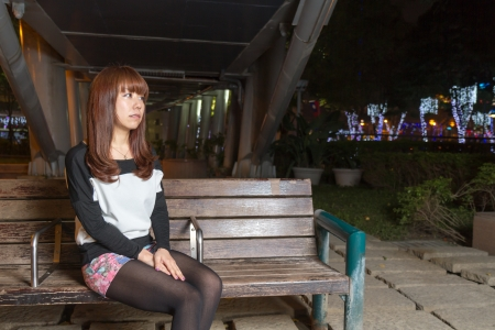 Japanese female looking sad sitting on a brown park bench photo