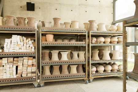 ceramicist: Clay cermaic pots on shelves at pottery studio