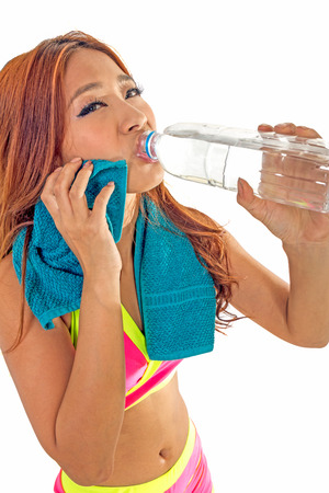 Beautiful Chinese woman with water bottle and towel after workout photo