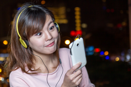 Attractive Malaysian Woman With Yellow Headphones holding cellphone photo