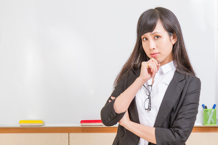 Chinese teacher in front of whiteboard dressed formal, deep in thought photo