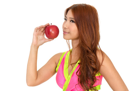 Sporty Asian woman in exercise clothes holding an apple photo