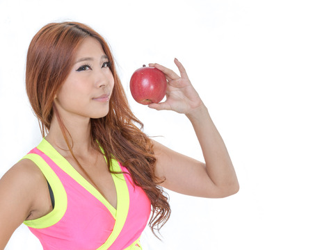 Sporty Asian woman in exercise clothes holding an apple
