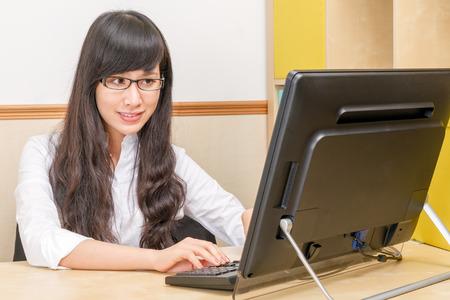 Asian businesswoman at computer desk Stock Photo