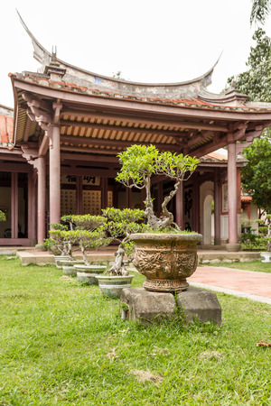 A Confuscius temple with bonsai plansts in front