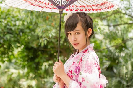 Chinese lady wearing kimono in traditional Japanese style garden photo