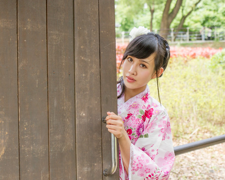 Asian woman in a kimono in a Japanese style garden, opening a door photo
