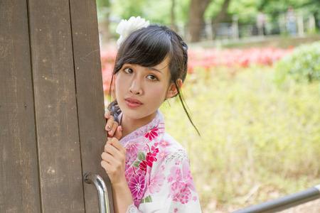 Asian woman in a kimono next to a door in a Japanese style garden photo