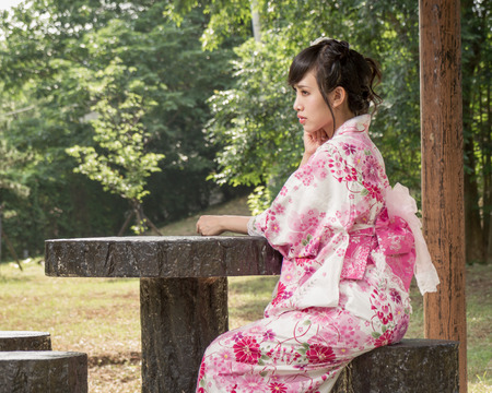 Asian woman in a kimono sitting in a Japanese style garden