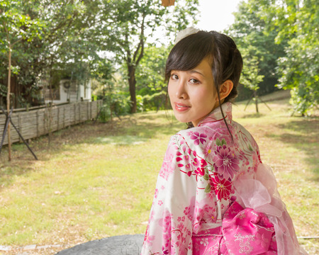 Asian woman in a kimono in a Japanese style garden looking back at camera photo
