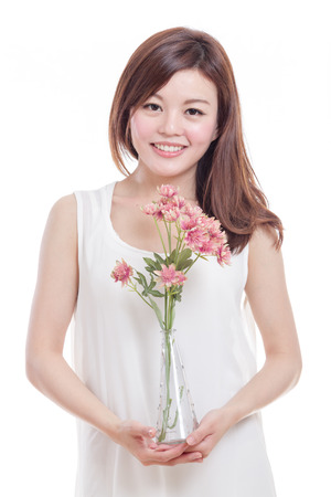 Beautiful Malaysian woman with pink flowers in a vase photo