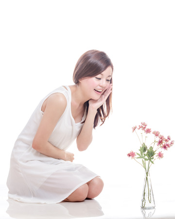 Beautiful Malaysian woman looking at pink flowers in a vase photo
