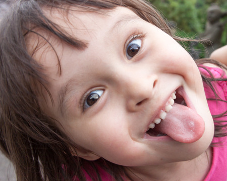 in out: Child making funny face and sticking tongue out Stock Photo