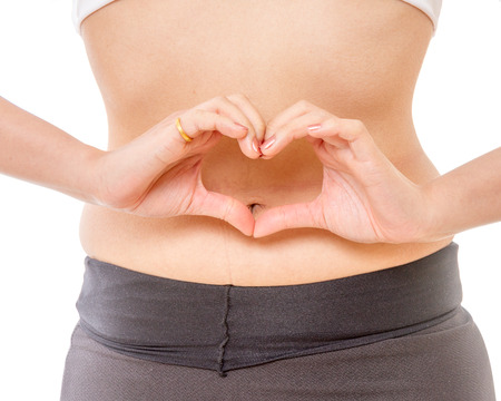 Woman making heart shape with her hands on her stomach
