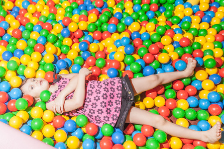 playcentre: Young girl plaing in colorful pool of balls