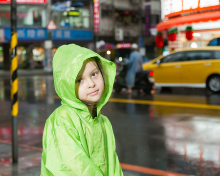 Young girl in rain wearing a green raincoat next to a city street