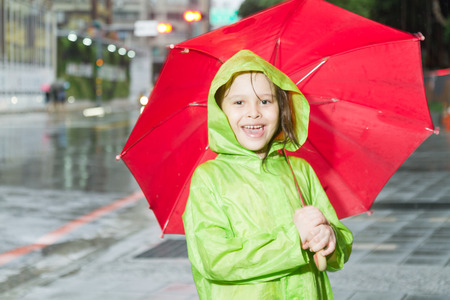 Young girl in rain wearing a green raincoat and holding a red umbrella on sidewalk next to street photo