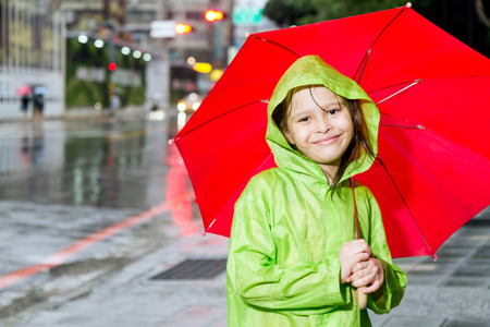 Young girl in rain wearing a green raincoat and holding a red umbrella on sidewalk next to street