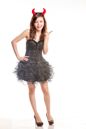 Asian female in devil halloween costume pointing finger photo