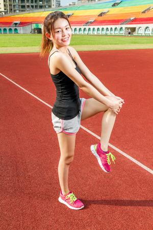 female jogger: Basculador estirar las piernas femeninas de Asia en el campo de deportes de calentamiento Foto de archivo