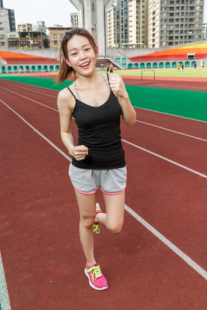 Asian Chinese woman at stadium jogging Stock Photo