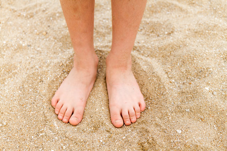 Bare feet of a young child in the sand
