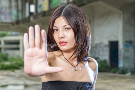 Chinese woman showing no hand gesture with old bulding in background