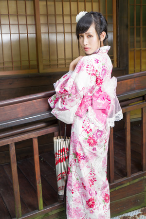 Asian woman wearing a kimono in front of  Japanese house holding umbrella, looking back over shoulder photo