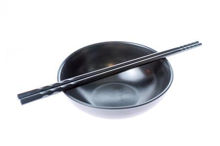 Chinese or Japanese chopsticks on empty black bowl