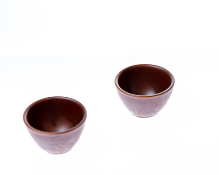 Asian ceramic cups for sake or soju on white background