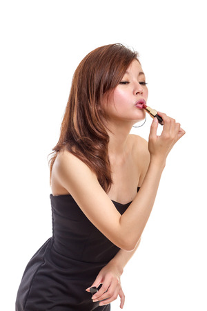 Chinese woman in black dress putting on lipstick
