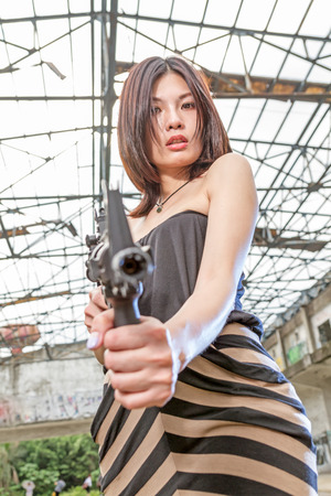 Chinese woman with sub-machine gun by abandoned building