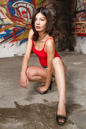 squatting down: Beautiful Chinese woman squatting down by walls filled with graffiti Stock Photo