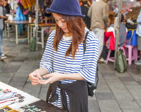Chinese woman looking at jewelry vendor at a street market in Taipei, Taiwan