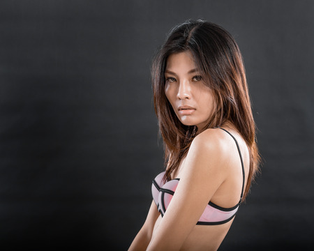 erotical: Chinese woman wearing pink and black underwear on black background Stock Photo