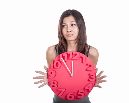 five to twelve: Worried Chinese woman holding clock showing five to twelve Stock Photo